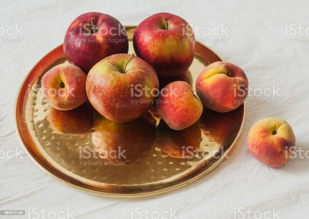 Red summer fruits on a golden dish and white background royalty-free stock photo