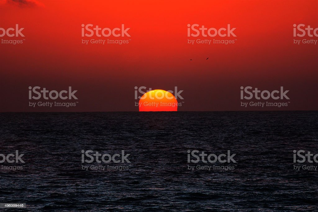 Red sun dives into the ocean - inferior mirage stock photo