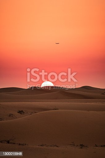 Red sun setting over the sand dunes in a middle eastern arid desert