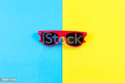 istock Red sunglasses on bright blue and yellow background. 908571446