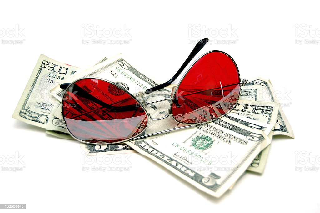 Red sunglasses resting on cash stock photo