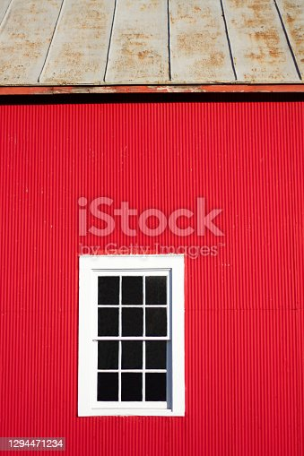 Red Sunlit Midwest Barn with White Window Close-Up