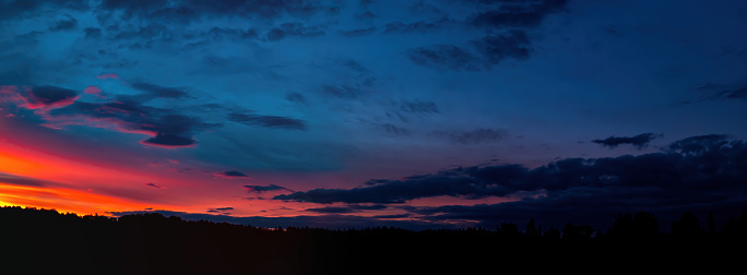 Red sunny sunset with thunderclouds on the horizon. Sky with clouds. Sunny sunset. Cloudy horizon. Forest in the dark. Evening twilight. Night time. Weather. Natural landscape. Panoramic photo.