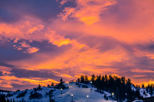 Red sunset in Colorado ski resort Colorful view of Colorado ski slope with running chairlift at sunset; dramatic sun above the mountain steamboat springs stock pictures, royalty-free photos & images