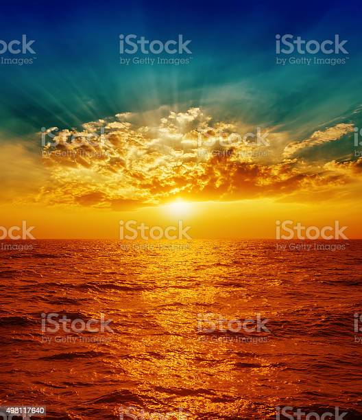 Photo of red sunset over sea in clouds