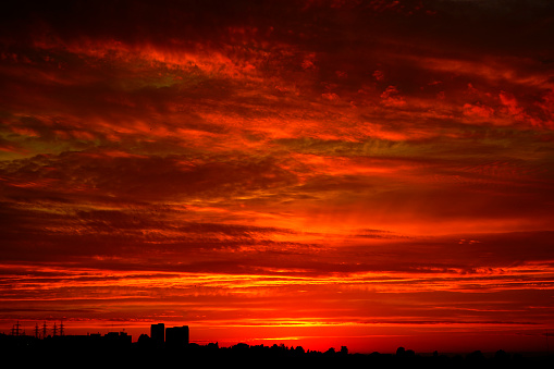Red sunset over the city. Black red abstract background. Dramatic sky. Dark red horror background. Blood red sunset. Armageddon.