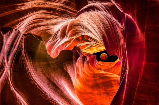 red supermoon eclipse in Upper Antelope Canyon Composite with Red full moon eclipse outside Upper Antelope Canyon navajo sandstone formations stock pictures, royalty-free photos & images