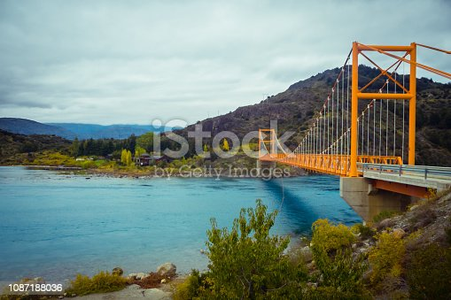 istock Red suspension bridge over the water runoff of General Carrera Lake, near Lake Bertrand, Puerto Tranquilo, Chile Chico, Aysen, Chile 1087188036
