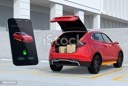 istock Red SUV in parking lot with opened trunk, cardboard boxes inside. Smartphone app on the left for unlock the car trunk 956056962