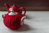Red sweater cozy teapot and red teapot on wooden background