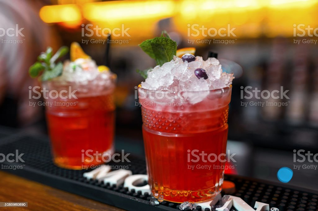 Red sweet alcoholic cocktails in a glass with ice cubes with vodka martini and decorated with mint leaves and berries in the bar. Club life. Original cocktails. Close-up stock photo