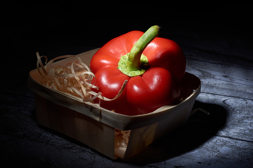 red sweet pepper in a straw basket on a black background.