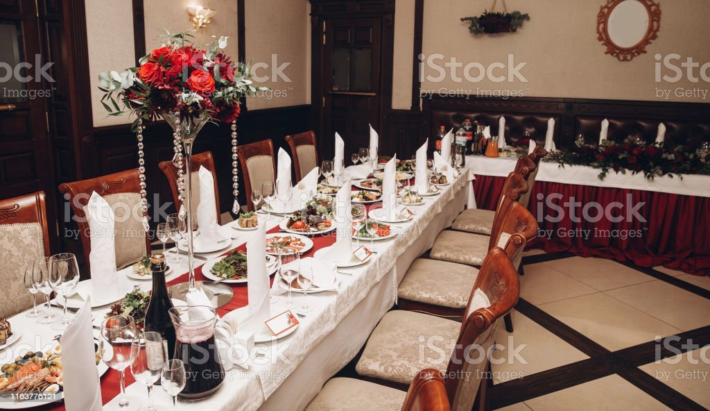 red table centerpiece with bouquet and food for wedding couple at...