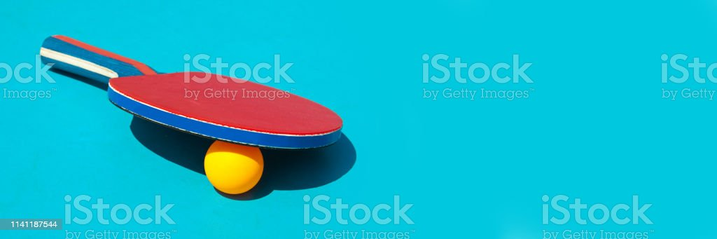Red table tennis racket and ball on blue panoramic background whith...