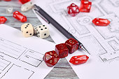 Red tabletop role playing RPG game dices on blurry hand drawn dungeon map and character sheet