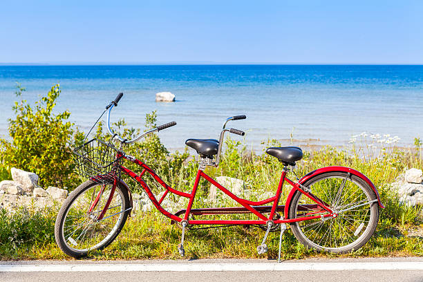 red tandem bicycle on the side of a road by a beach - mackinac island stock photos and pictures