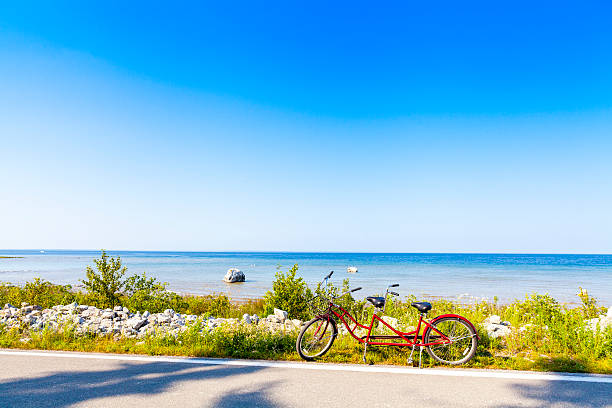 a red tandem bike parked on a beach road - mackinac island stock photos and pictures