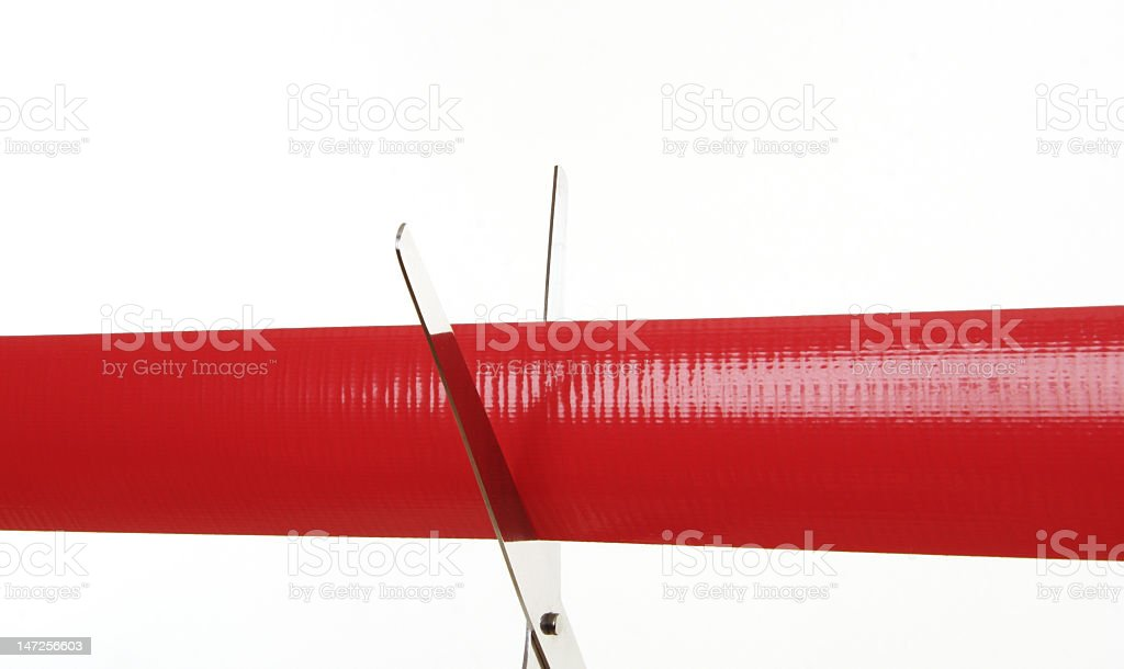 Red tape being cut by a pair of safety scissors royalty-free stock photo
