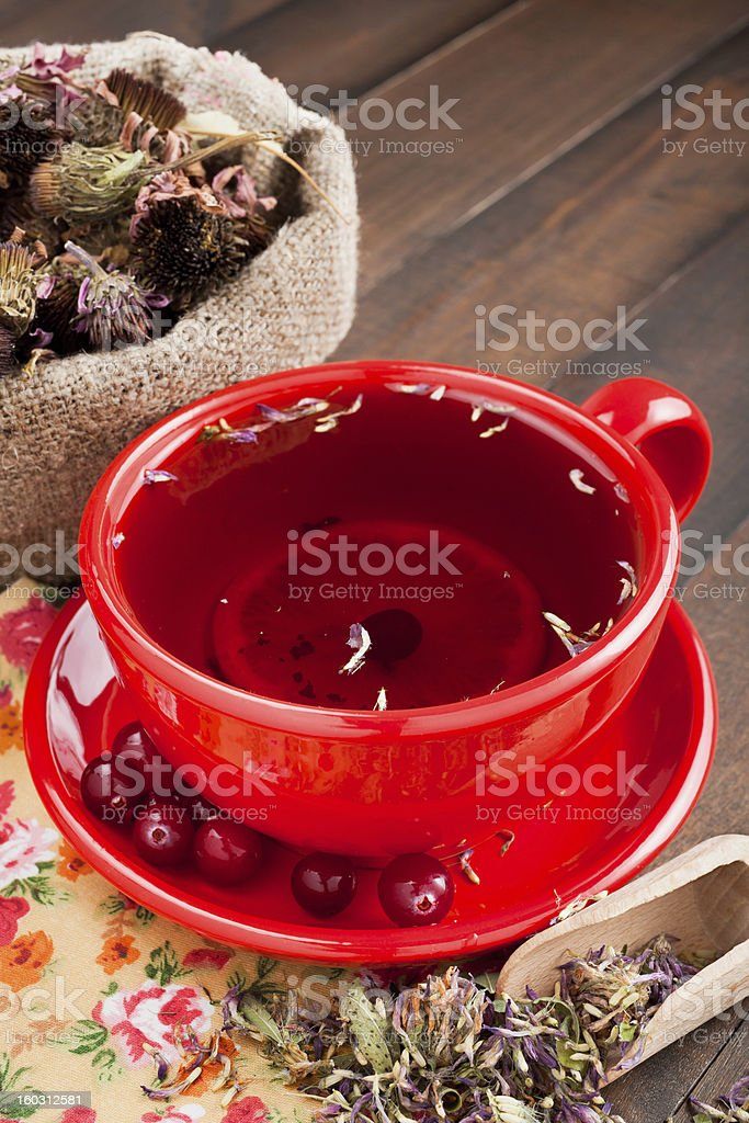 red tea cup, healing herbs on kitchen table royalty-free stock photo