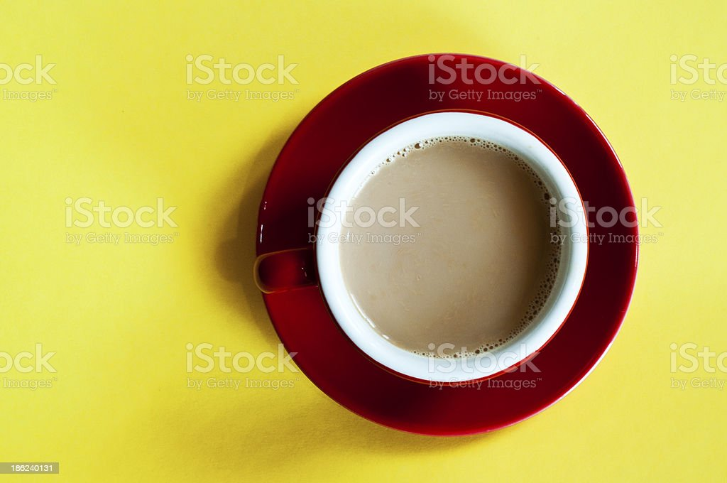 Red tea cup with saucer on table against yellow background royalty-free stock photo