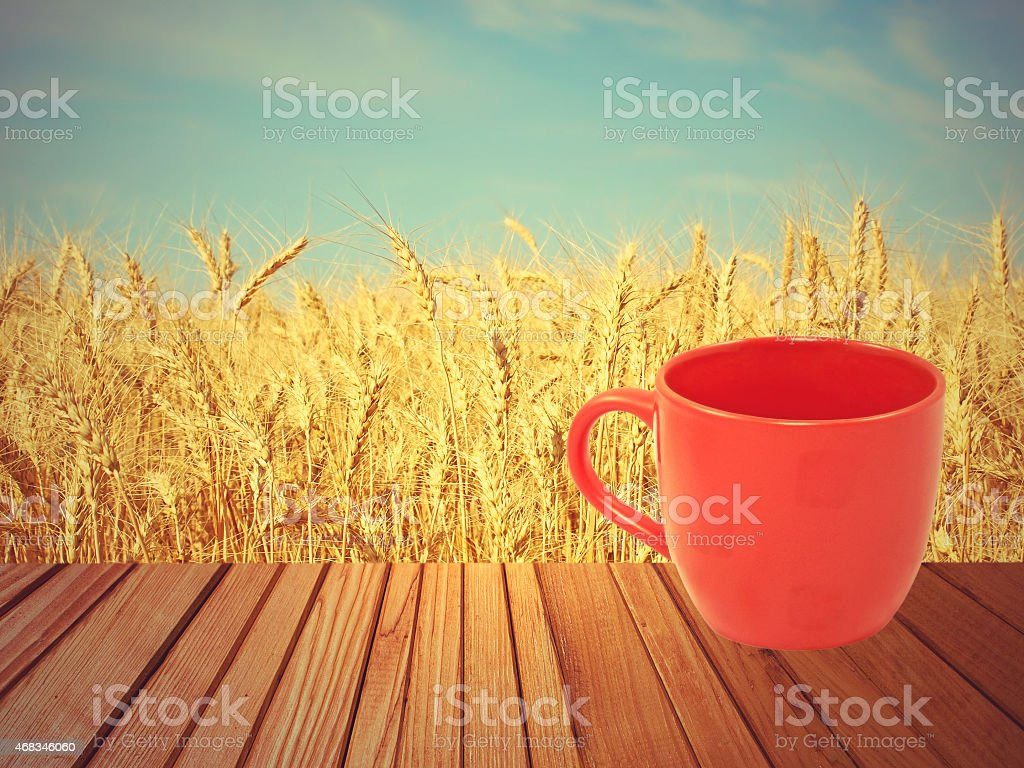 Red tea mug on wooden surface against wheat. royalty-free stock photo