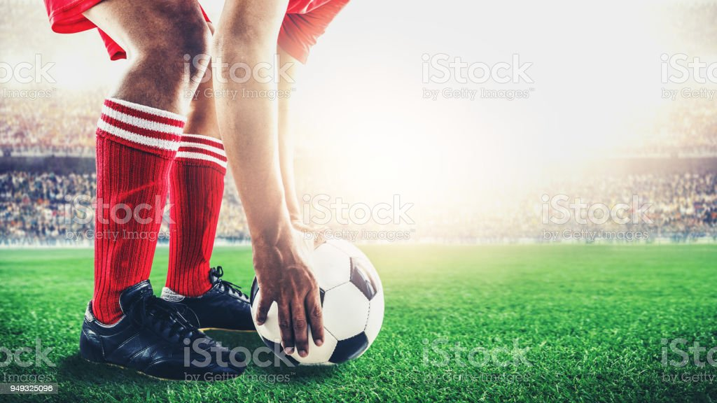 red team soccer footballer get the ball to free kick or penalty kick during match in the stadium stock photo