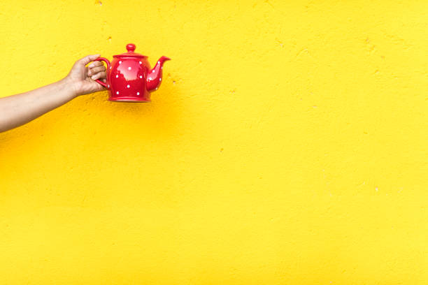 Red teapot on yellow background stock photo