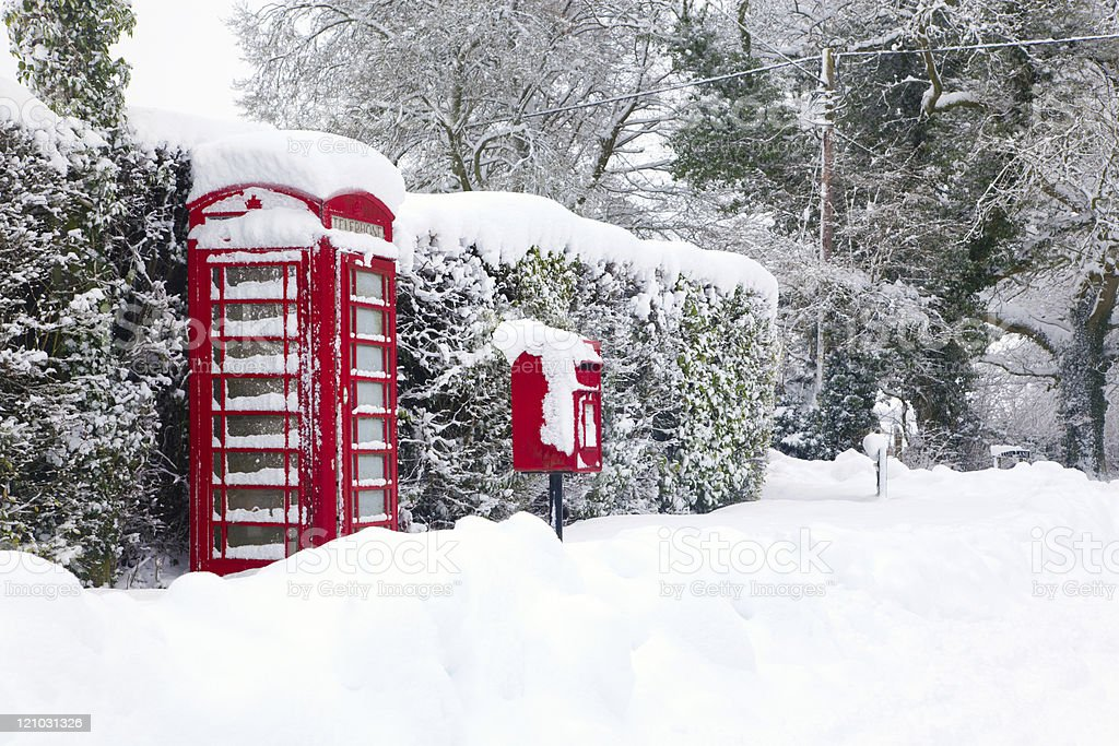 Red telephone and post box in the snow stock photo