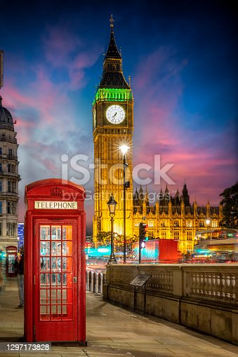 Red telephone booth in front of the illuminated Big Ben clocktower in London, United Kingdom, just after sunset with street traffic