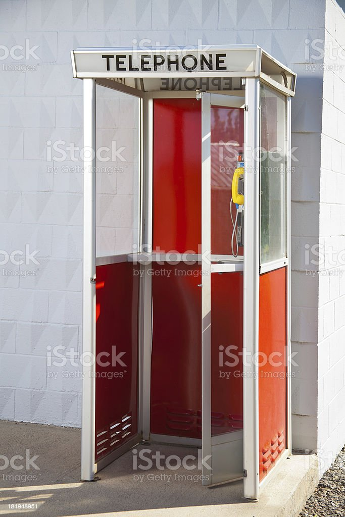 Red telephone booth on a street corner with  glass door royalty-free stock photo