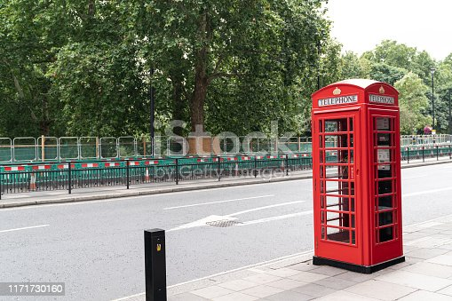 Classic red telephone booth on sidewalk in street of London, UK. No recognizable people in frame. Shot under daylight with a full frame mirrorless camera.