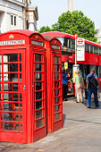 London, United Kingdom -June 21, 2017:   Red telephone booth on the street in the city.The red telephone box( telephone kiosk) is one of the symbols of UK, used since about 1920