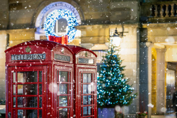 Red telephone booths in front of Christmas decorations lights in London, United Kingdom stock photo