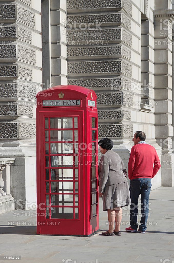 Red Telephone Box And A Curious Tourist royalty-free stock photo