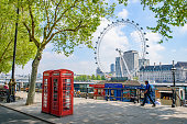 Red telephone box at the north bank of the River Thames with London Eye at background in London, United Kingdom