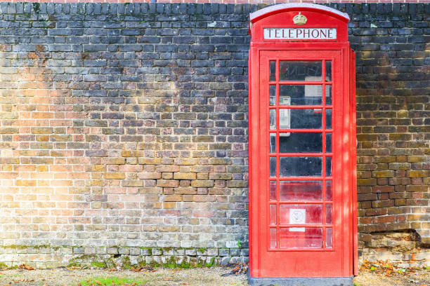 Red telephone box on street of Hampstead Heath in London against a grungy brick wall stock photo