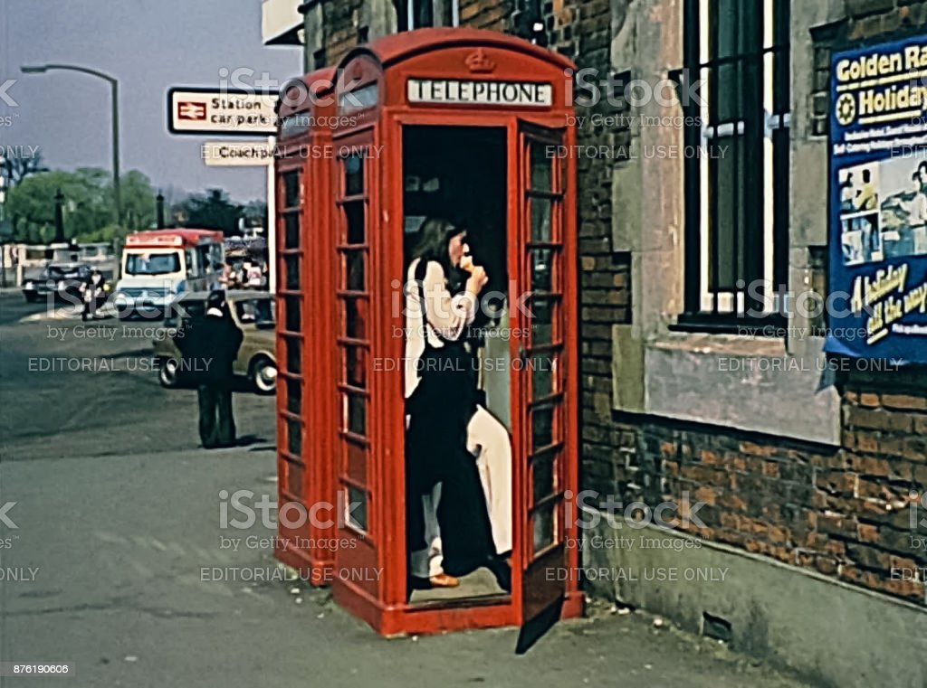 Red telephone box LONDON, UNITED KINGDOM - CIRCA 1979: Red telephone box with woman in vintage clothing in Oxford street. Historic 1970s image 1970-1979 Stock Photo