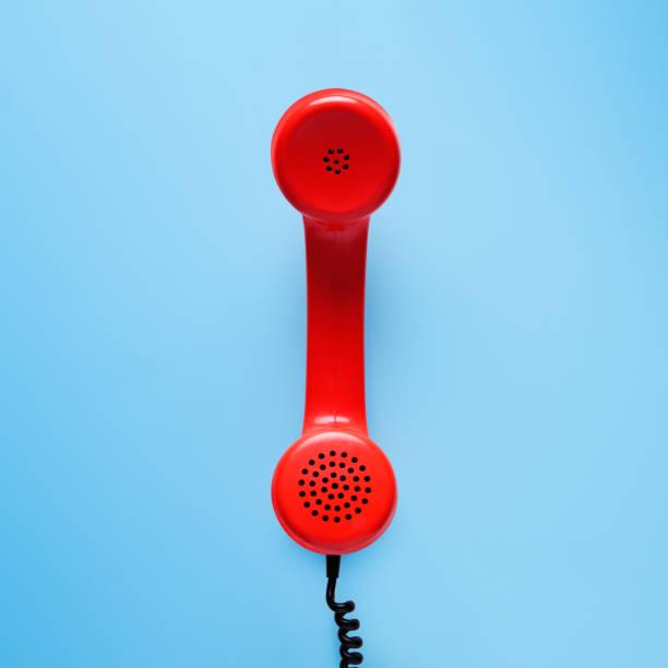 red telephone in retro style on blue background. - cornetta telefono foto e immagini stock