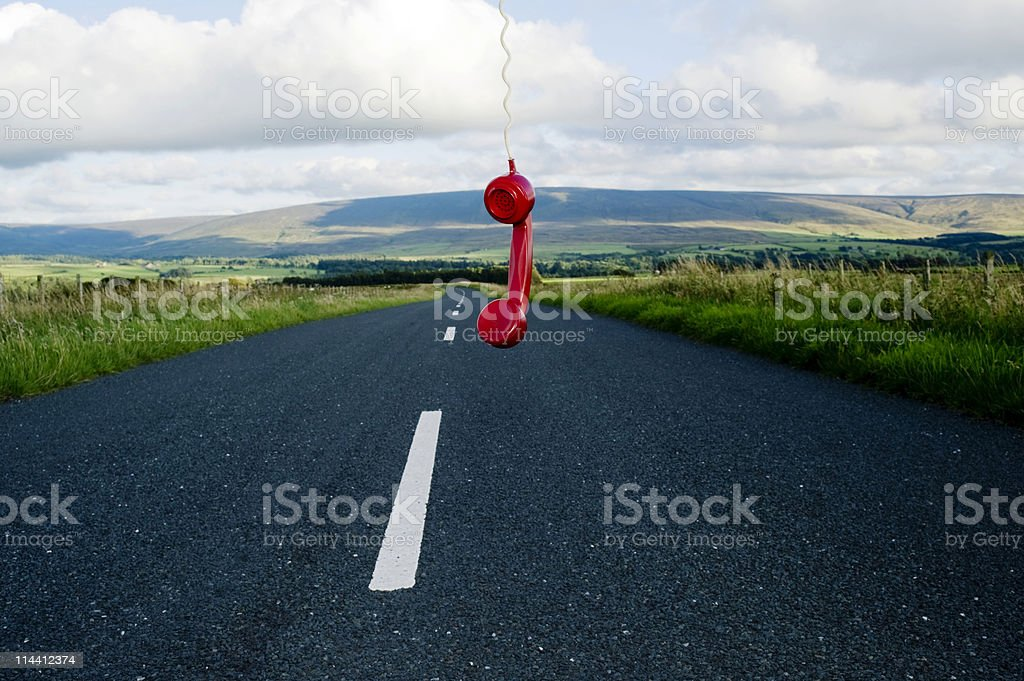 red telephone receiver hanging in the road.