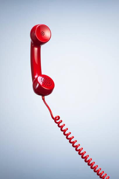 red telephone receiver with hanging cable isolated beautiful studio background. - cornetta telefono foto e immagini stock