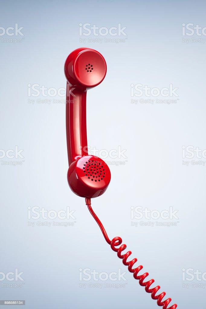 Receptor de telefone vermelho com suspensão cabo isolado fundo bonito Studio. - foto de acervo