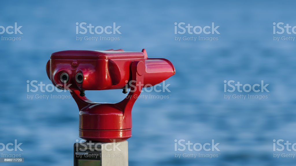 A red telescope on the shore of the lake constance in germany in front of blue water stock photo