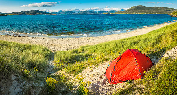 Red tent camping on idyllic island beach summer ocean panorama stock photo