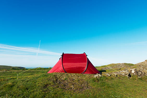 red tent in a remote position by the sea. - tent stock pictures, royalty-free photos & images