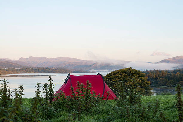 red tent on a hill overlooking a lake - tent stock photos and pictures