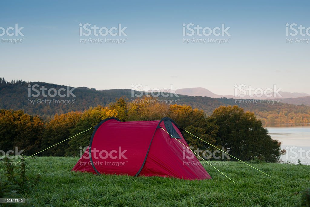 red Tent on a hill overlooking a lake stock photo