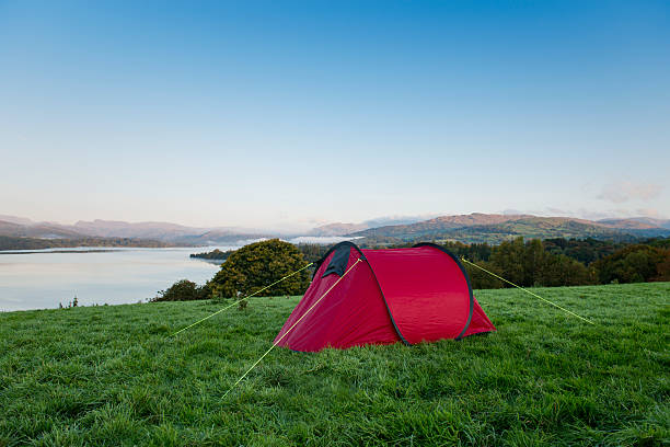 red tent on a hill overlooking a lake - tent stock pictures, royalty-free photos & images