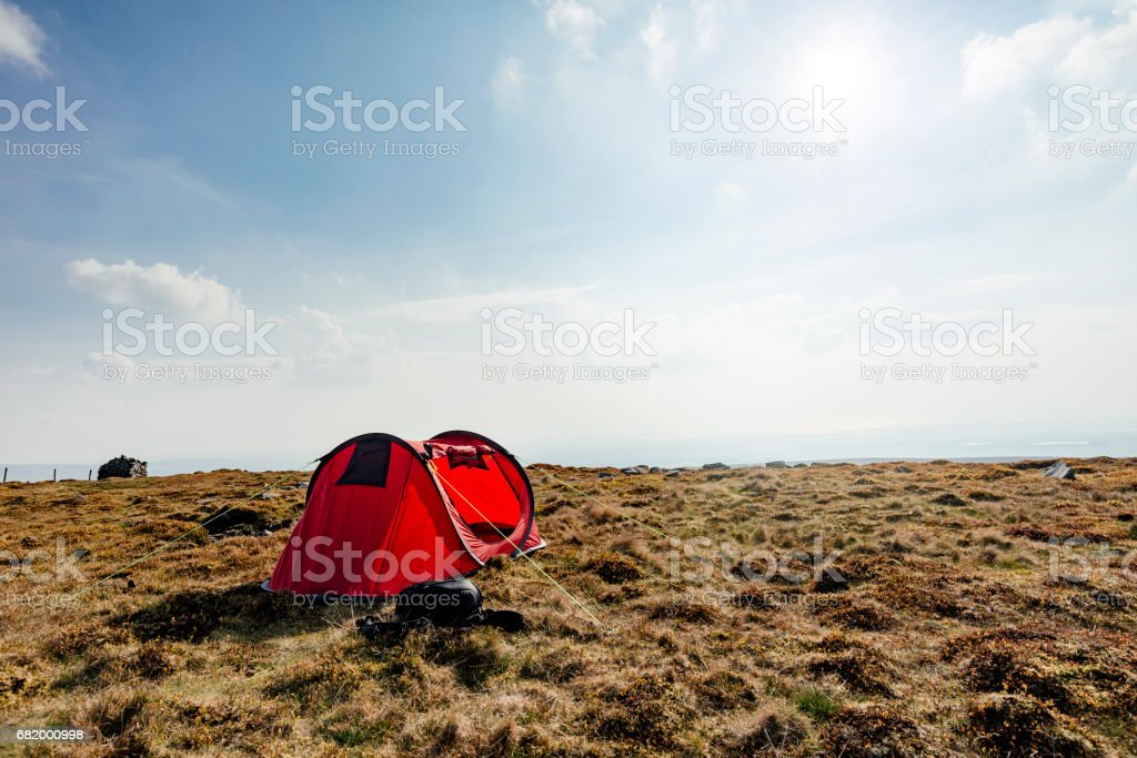 red tent set up in a remote location. stock photo