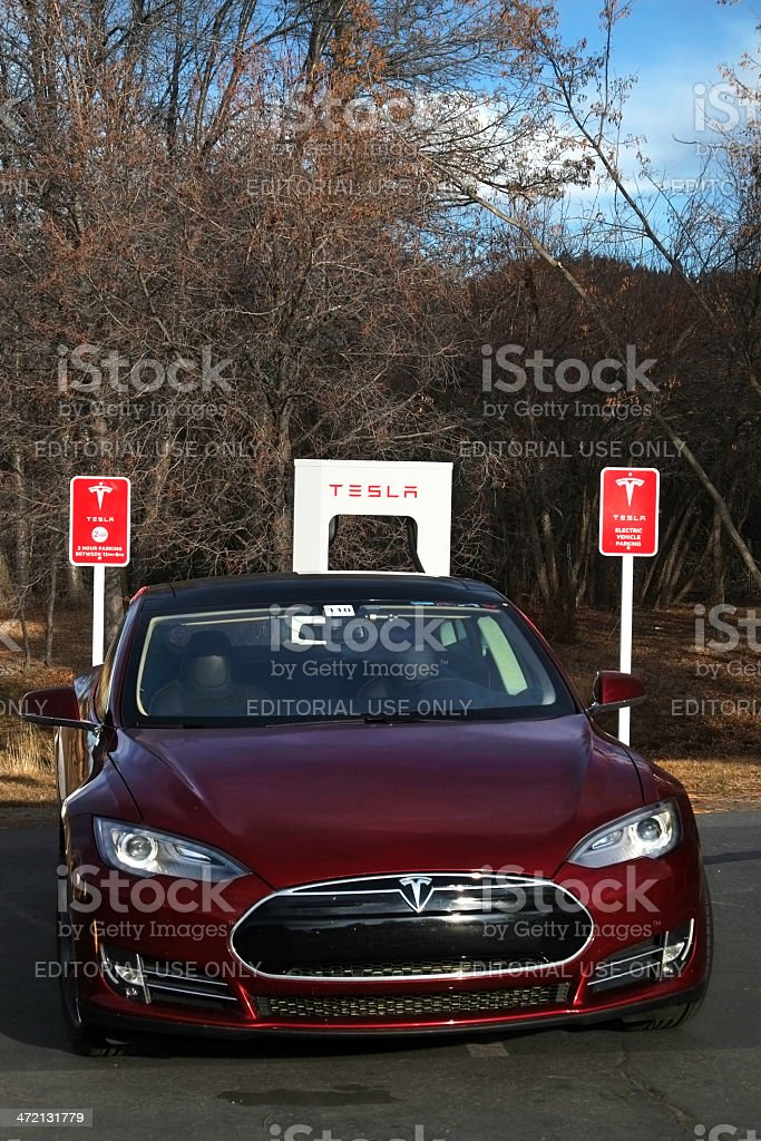 Red Tesla Car at Supercharger Station royalty-free stock photo