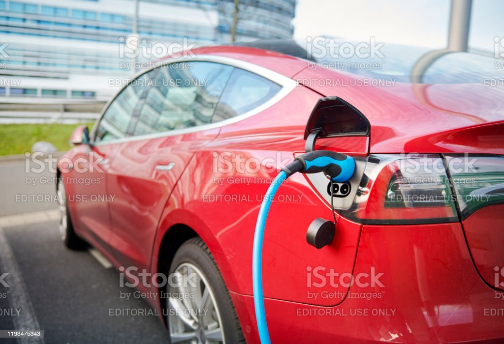 Red Tesla Model S electric car connected to a recharging station Duesseldorf, Germany- December 10. 2019: A red Tesla Model S is parked in a business destrict of Duesseldorf and is connected with a blue power chord to a recharging station, a modern office buidling in the background. 2019 Stock Photo